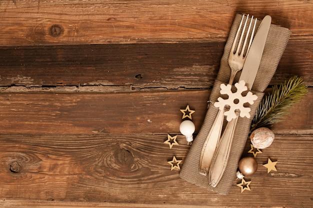 Hoge hoek shot van bestek set met landelijke stijl servet en kerstversiering op houten oppervlak Gratis Foto