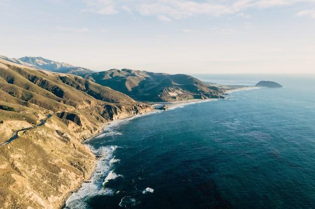 Hoge hoek shot van de oceaan op een rotsformatie bedekt met groen Gratis Foto