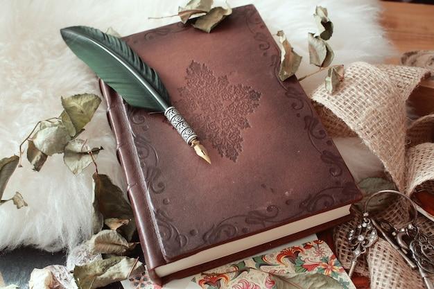 Hoge hoek shot van een ganzenveer op een oud boek bedekt met gedroogde bloemblaadjes Gratis Foto