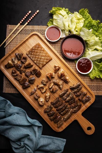 Hoge hoek shot van een houten dienblad met gebakken vlees, aardappelen, groenten en saus op een zwarte tafel Gratis Foto