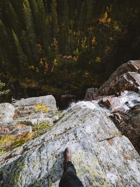 Hoge hoek shot van een persoon die op een rots bovenop een waterval in noorwegen staat Gratis Foto