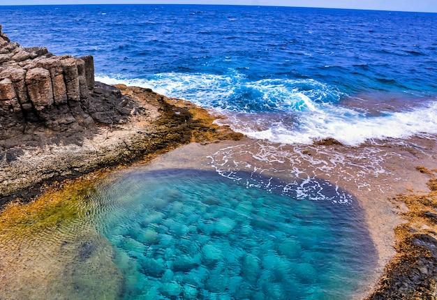 Hoge hoek shot van een prachtige zee, omringd door rotsformaties op de canarische eilanden, spanje Gratis Foto