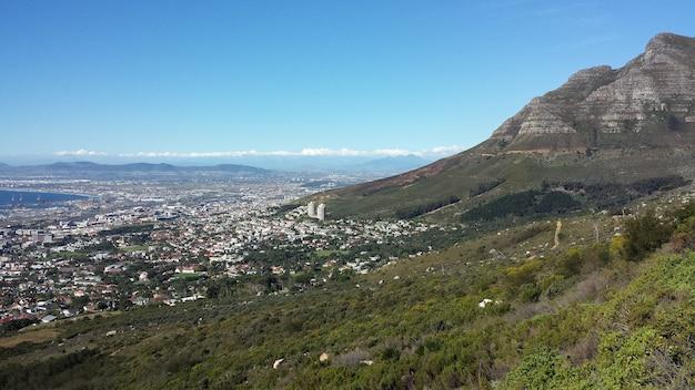 Hoge hoek shot van een stad aan de voet van een prachtige berg onder een heldere blauwe hemel Gratis Foto