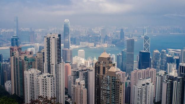 Hoge hoek shot van een stadsgezicht met veel hoge wolkenkrabbers onder de bewolkte hemel in hong kong Gratis Foto