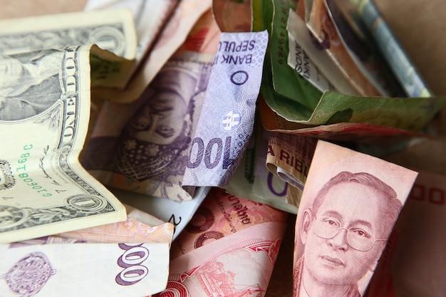 Hoge hoek shot van een stapel bankbiljetten uit verschillende landen op een houten oppervlak Gratis Foto