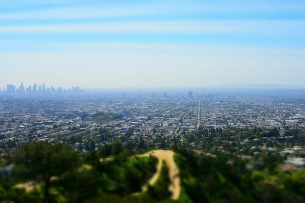 Hoge hoek shot van een stedelijke weergave met hoge gebouwen omringd door groen landschap Gratis Foto
