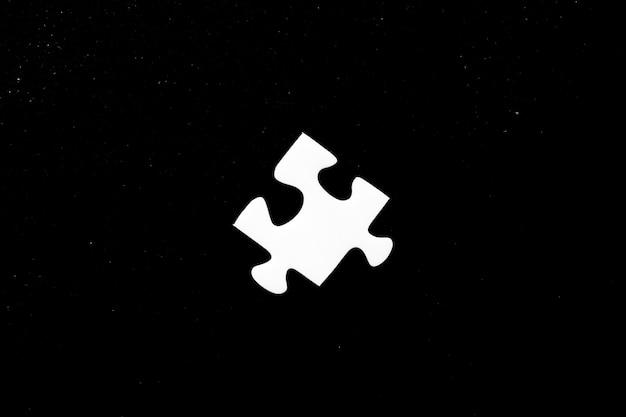 Hoge hoek shot van een wit stukje van een puzzel op een zwarte achtergrond Gratis Foto