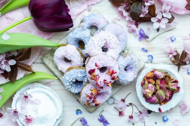 Hoge hoek shot van enkele blauwe en paarse veganistische donuts omgeven door bloemen op een tafel Gratis Foto