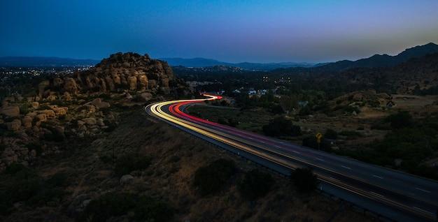 Hoge hoek shot van gele en rode lichten op de snelweg, omringd door rotsen 's nachts Gratis Foto