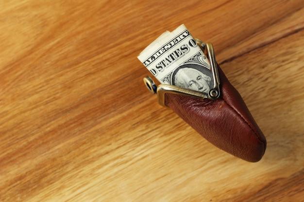 Hoge hoek shot van wat geld in een lederen portemonnee op een houten oppervlak Gratis Foto