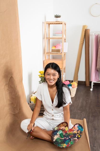 Hoge hoek smiley vrouw met palet Gratis Foto