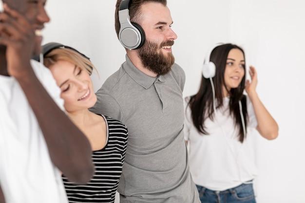 Hoge hoek smileyvrienden met hoofdtelefoons Gratis Foto