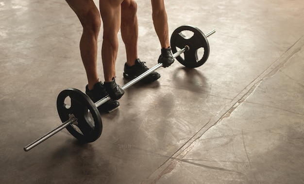Hoge hoek van anonieme mannelijke atleet barbell opheffen van vloer tijdens gewichtheffen training in de sportschool Premium Foto