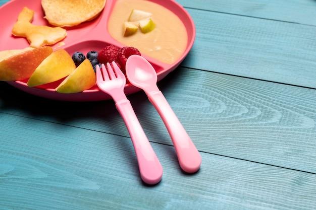 Hoge hoek van babyfruit op plaat met fruit Gratis Foto