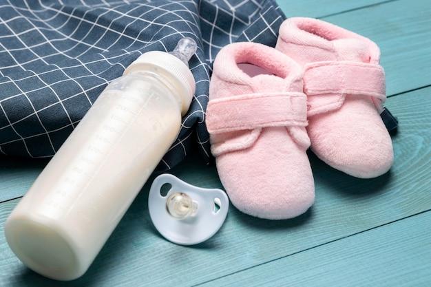Hoge hoek van babyschoentjes en fles met fopspeen Gratis Foto