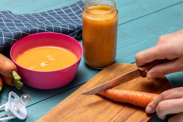 Hoge hoek van babyvoeding met wortelen en fopspeen Gratis Foto