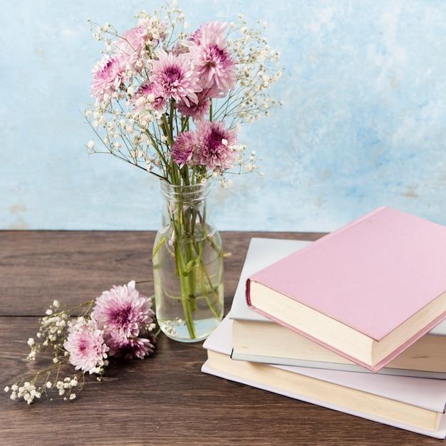 Hoge hoek van boeken en bloemen op houten tafel Gratis Foto