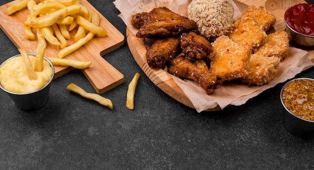 Hoge hoek van frietjes en gebakken kip Gratis Foto