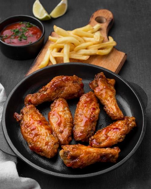 Hoge hoek van gebakken kip met frietjes Premium Foto