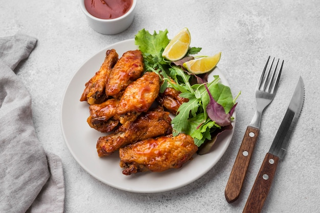 Hoge hoek van gebakken kip op plaat met salade en bestek Premium Foto