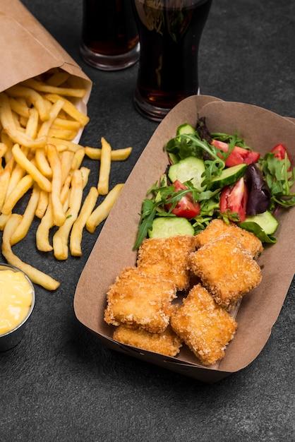 Hoge hoek van gebakken kipnuggets met frietjes en salade Gratis Foto