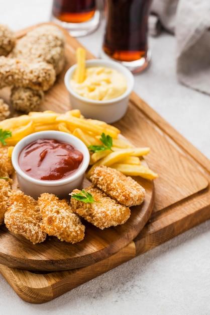 Hoge hoek van gebakken kippenpoten en nuggets met koolzuurhoudende dranken en frietjes Gratis Foto