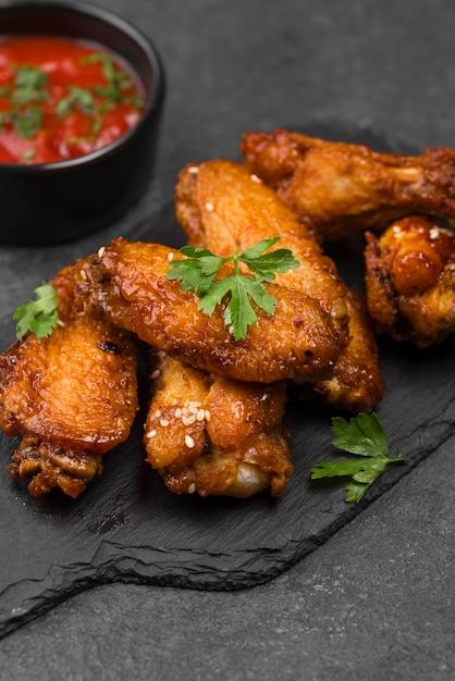 Hoge hoek van gebakken kippenvleugels op leisteen met saus Premium Foto