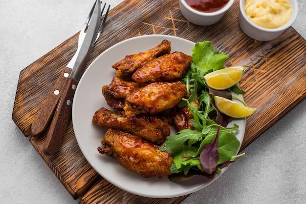 Hoge hoek van gebraden kip op plaat met bestek en saus Premium Foto
