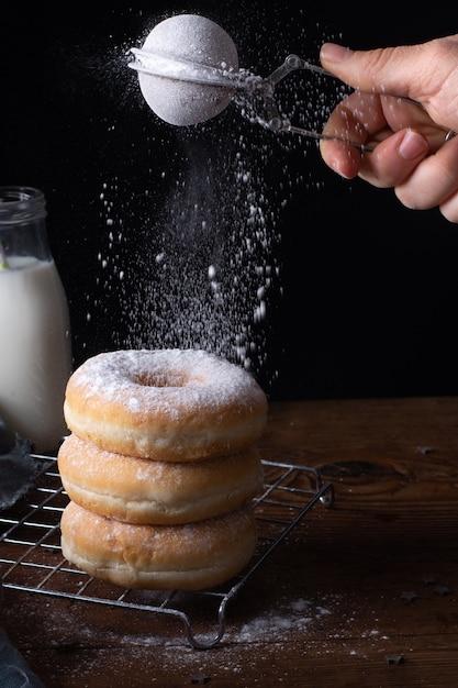 Hoge hoek van gestapelde donuts met hand glazuur ze met poedersuiker Gratis Foto