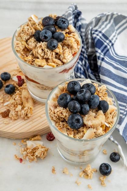 Hoge hoek van glazen met ontbijtgranen en yoghurt met fruit Gratis Foto