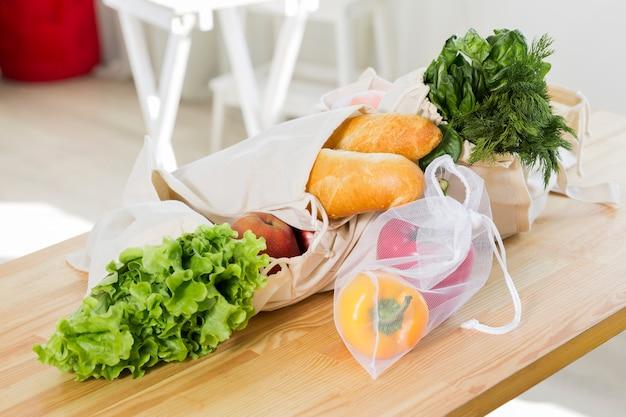 Hoge hoek van groenten en fruit op tafel met herbruikbare tassen Gratis Foto