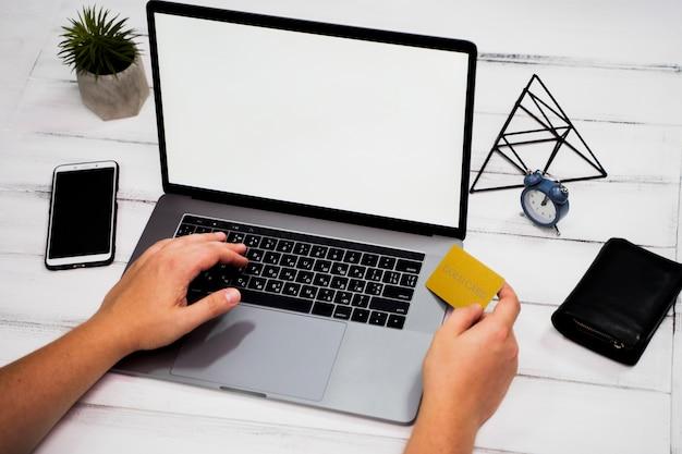 Hoge hoek van hand op laptop trefwoord op houten tafel Gratis Foto