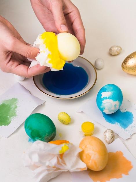 Hoge hoek van handen die ei verven voor pasen Gratis Foto