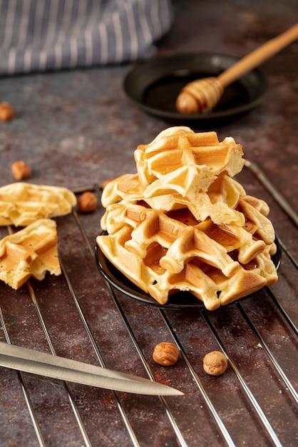 Hoge hoek van honing bedekt stapel wafels op plaat Gratis Foto