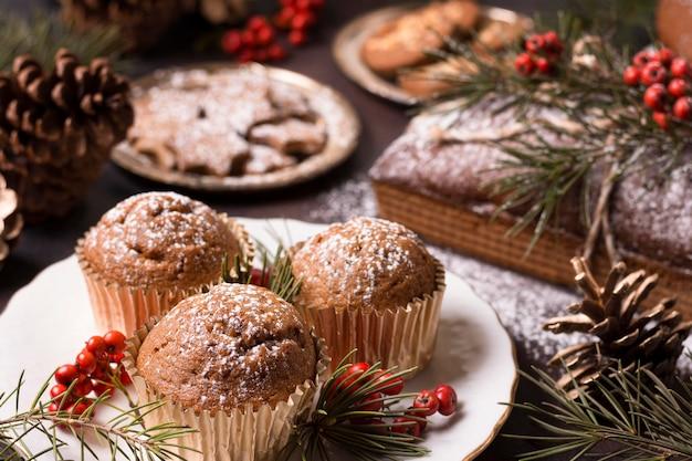 Hoge hoek van kerst cupcakes met koekjes en dennenappels Gratis Foto