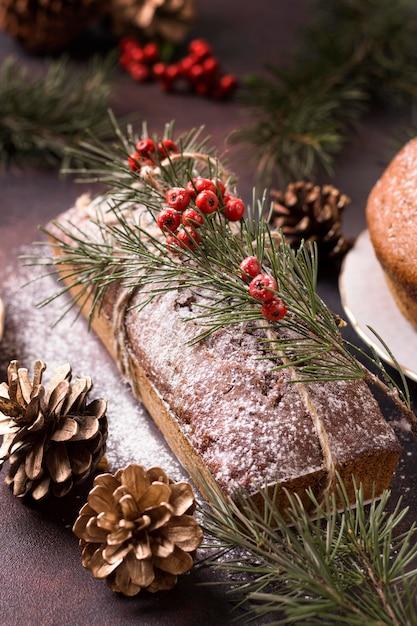 Hoge hoek van kerstmiscake met rode bessen en denneappels Gratis Foto