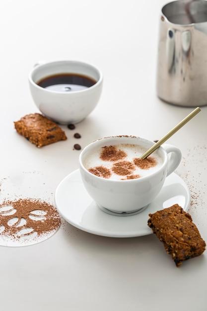 Hoge hoek van koffiekopjes met dessert en bord Gratis Foto