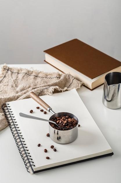 Hoge hoek van kop met koffiebonen op notitieboekje Gratis Foto