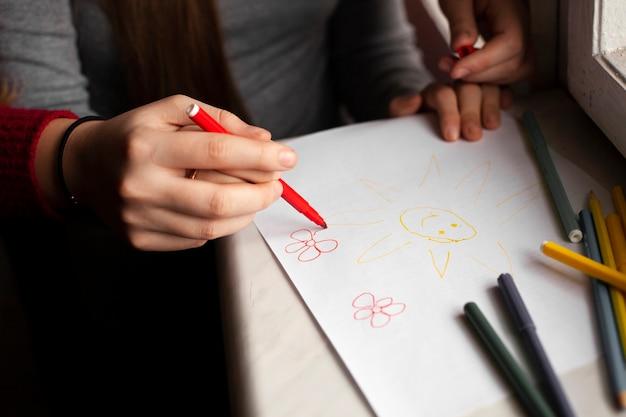 Hoge hoek van meisje met down syndroom en vrouw tekenen Gratis Foto
