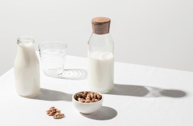 Hoge hoek van melkfles met leeg glas en kom met walnoten Gratis Foto