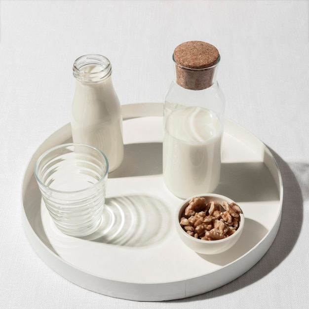 Hoge hoek van melkfles met walnoten op dienblad Gratis Foto