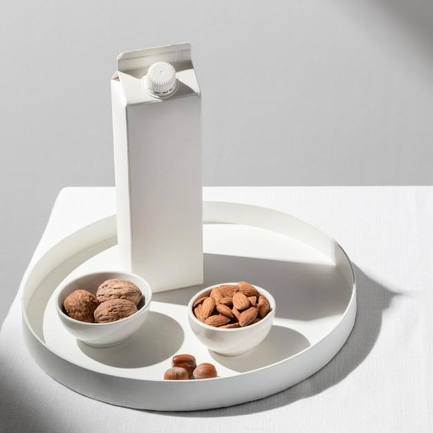 Hoge hoek van melkpak op dienblad met amandelen en walnoten Gratis Foto
