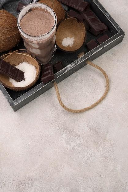 Hoge hoek van milkshakeglas op dienblad met kokosnoot en exemplaarruimte Gratis Foto