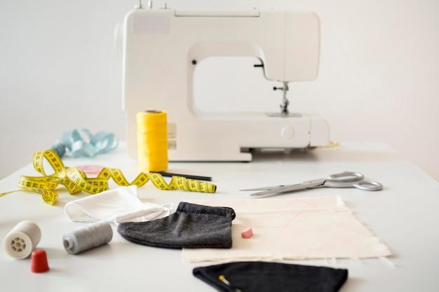 Hoge hoek van naaimachine met meetlint en gezichtsmaskers Gratis Foto