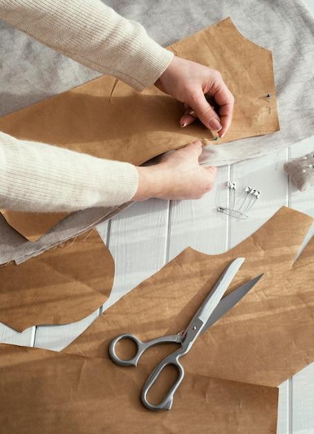 Hoge hoek van naaister met stoffen en schaar Gratis Foto