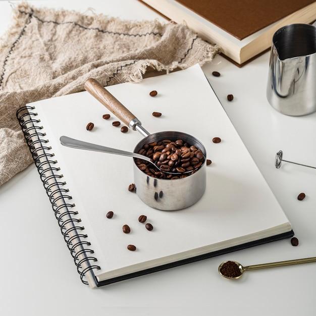 Hoge hoek van notebook met kopje gebrande koffiebonen Gratis Foto