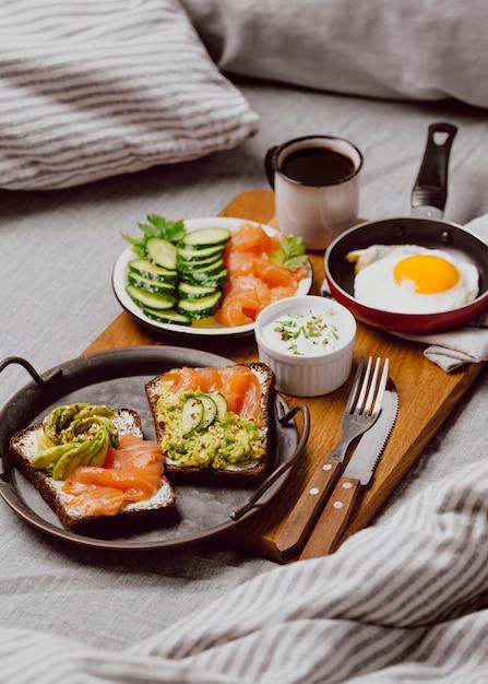 Hoge hoek van ontbijtsandwiches op bed met gebakken ei en toast Gratis Foto