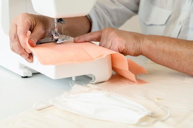 Hoge hoek van persoon naaien textiel met behulp van machine Gratis Foto