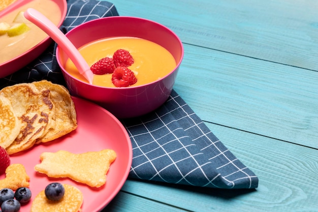 Hoge hoek van plaat met babyvoeding en fruit Gratis Foto