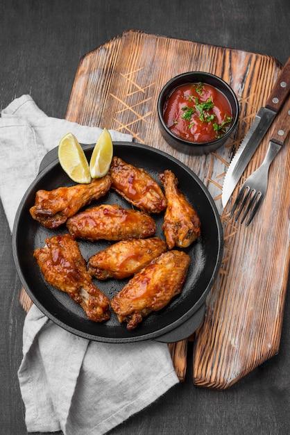 Hoge hoek van plaat met gebakken kip en saus Premium Foto
